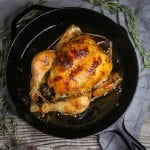 Overhead shot of perfect roast chicken in a cast iron pan with rosemary scattered around.