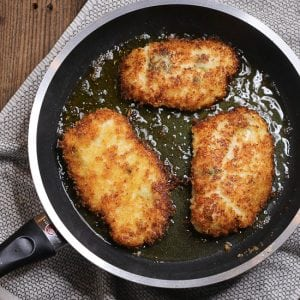 Close up of breaded chicken breasts cooking in a frying pan.