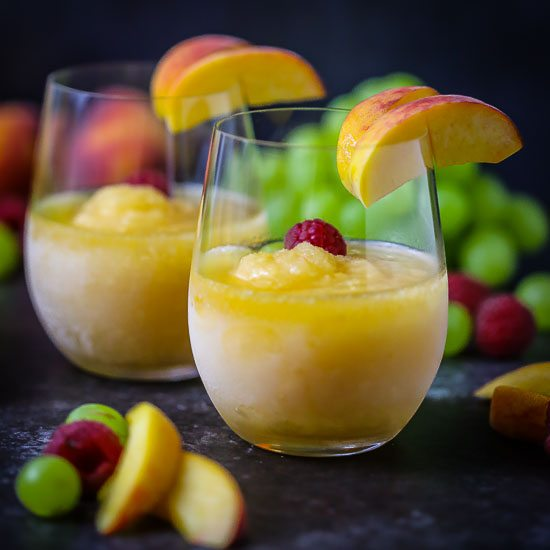 Close up shot of Peach Sangria Slushies garnished with peach wedges.
