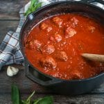 A pot of Sunday Sauce and Meatballs with a wooden spoon in the pot, a couple garden cloves and fresh basil alongside.