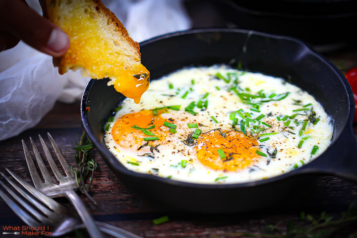 A piece of toast dipped in the yolk of Skillet Baked Eggs.