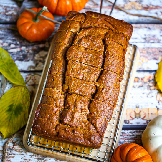 A sliced loaf of pumpkin bread on a cooling rack with pumpkins scattered around.