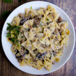 Close up of creamy farfalle pasta tossed with mushrooms and sausage in a creamy white wine sauce served in a white bowl.