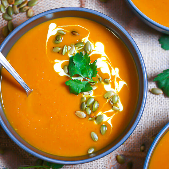 Close up of a bowl of Easy Curried Pumpkin Soup garnished with yogurt, pumpkin seeds and cilantro.